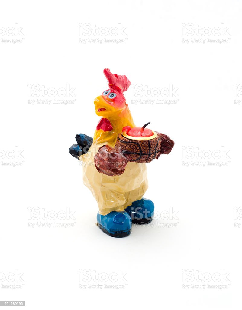 Toy rooster candleholder with a candle, isolated on white. stock photo
