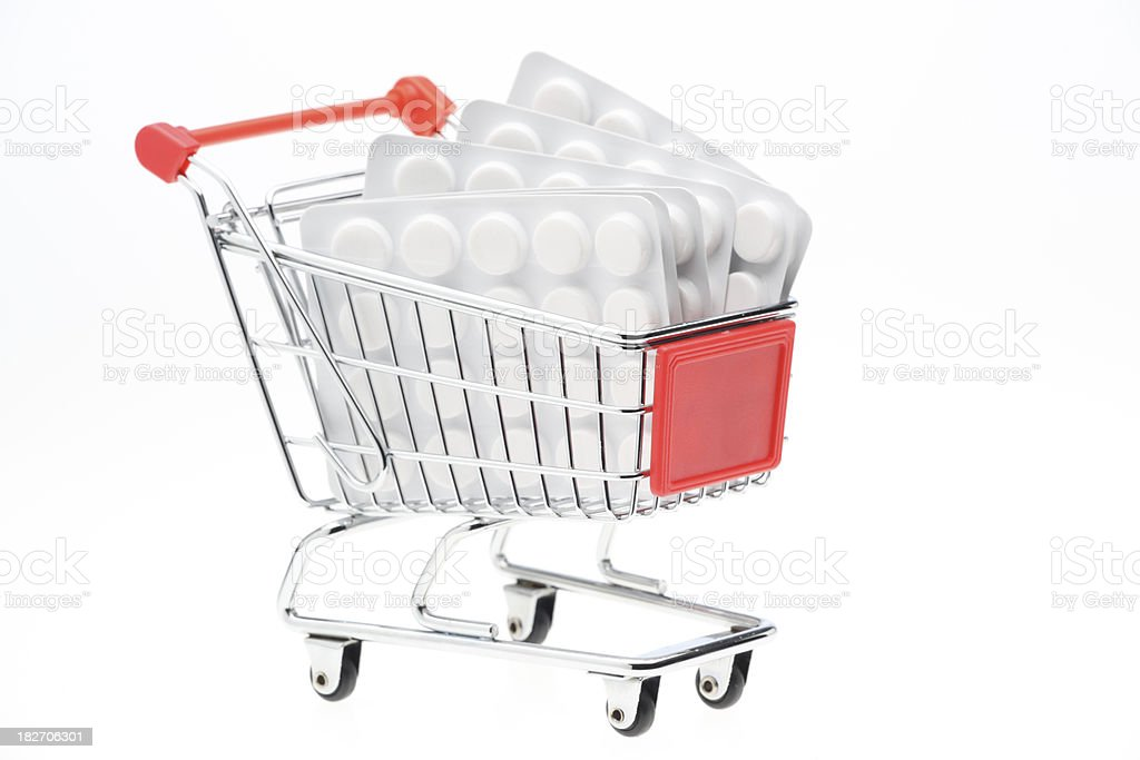 Toy shopping cart filled with white pills blister packs royalty-free stock photo