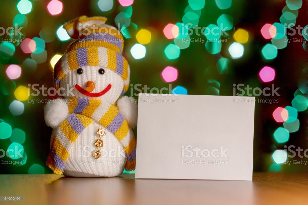 Toy snowman holding a sign for your text on  backgroun stock photo