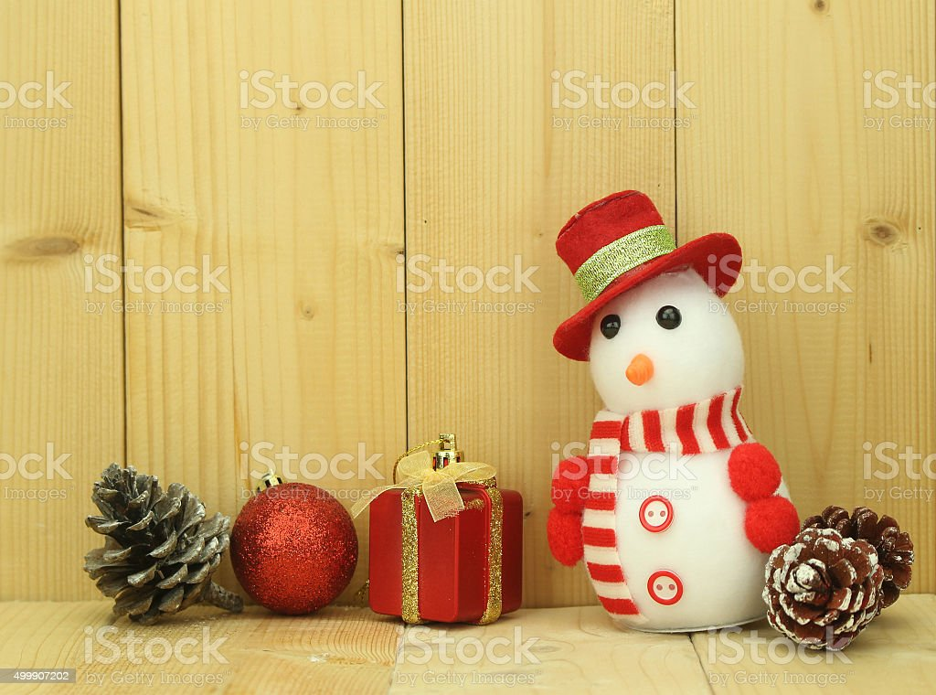 Toy snowman  is standing beside Christmas decoration stock photo