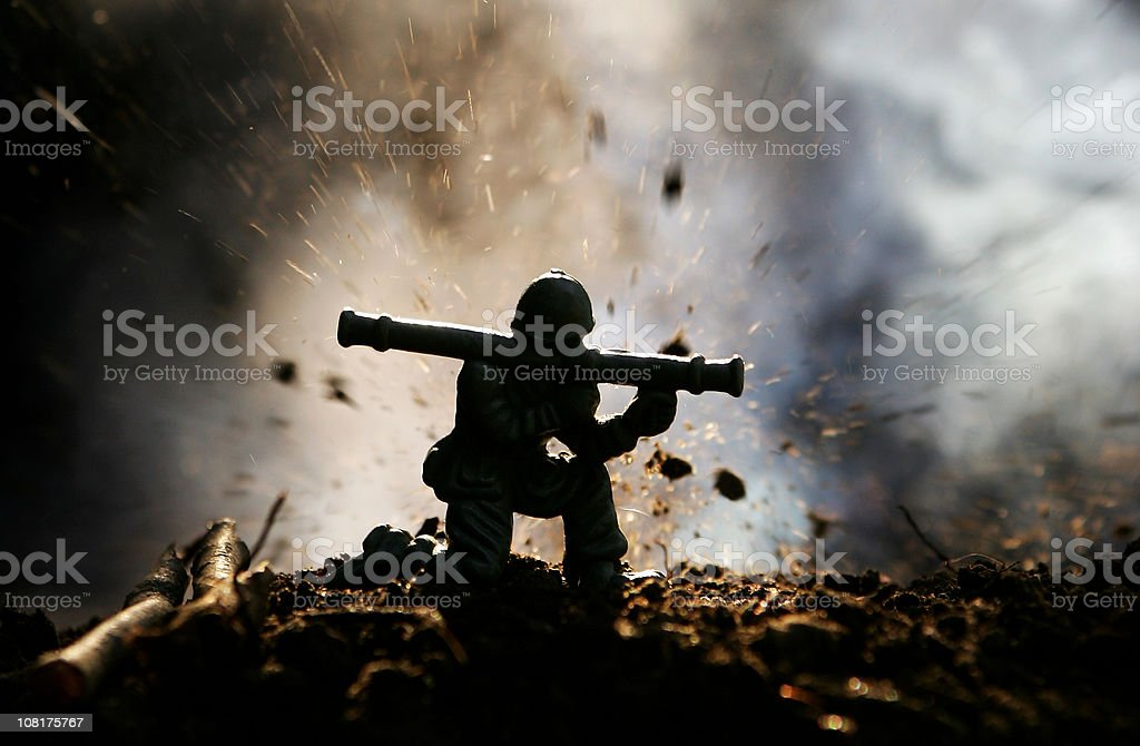 Toy Soldier fires a rocket launcher under attack stock photo