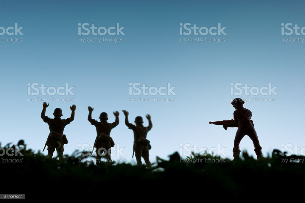 Toy soldiers surrender to an armed enemy stock photo
