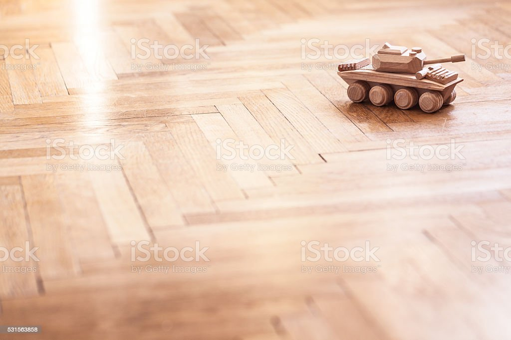 Toy tank on wooden floor. Vintage toy. Signs of war stock photo