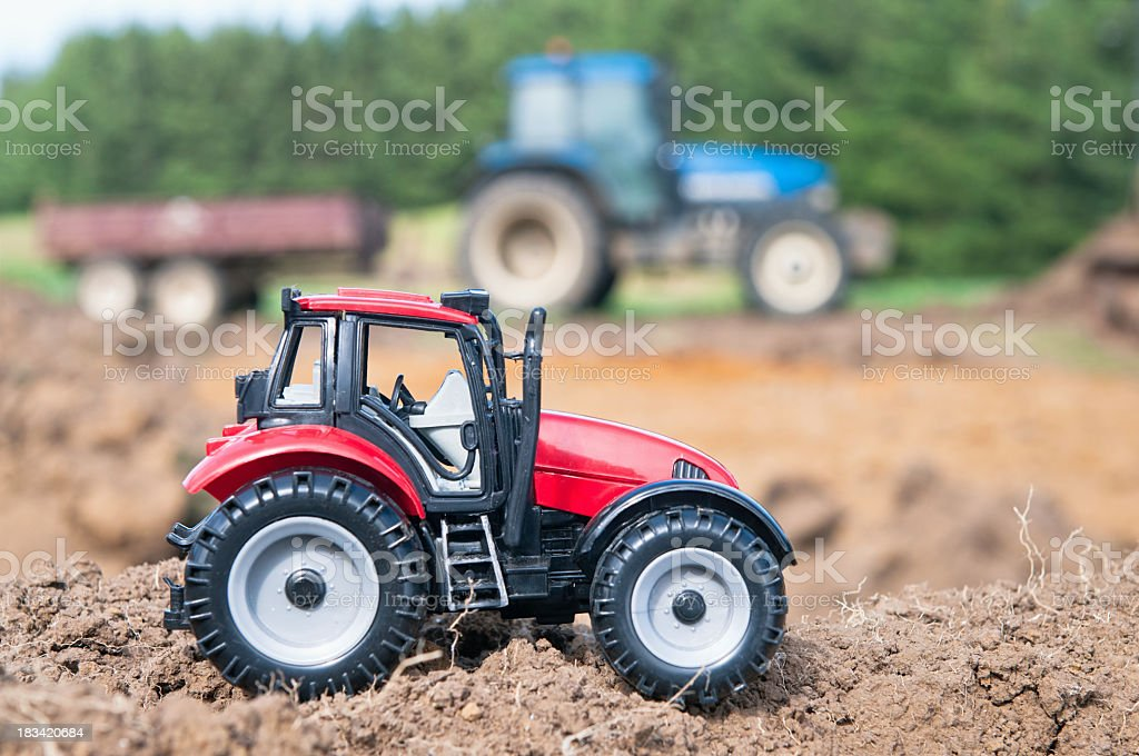Toy tractor compared to the real thing stock photo