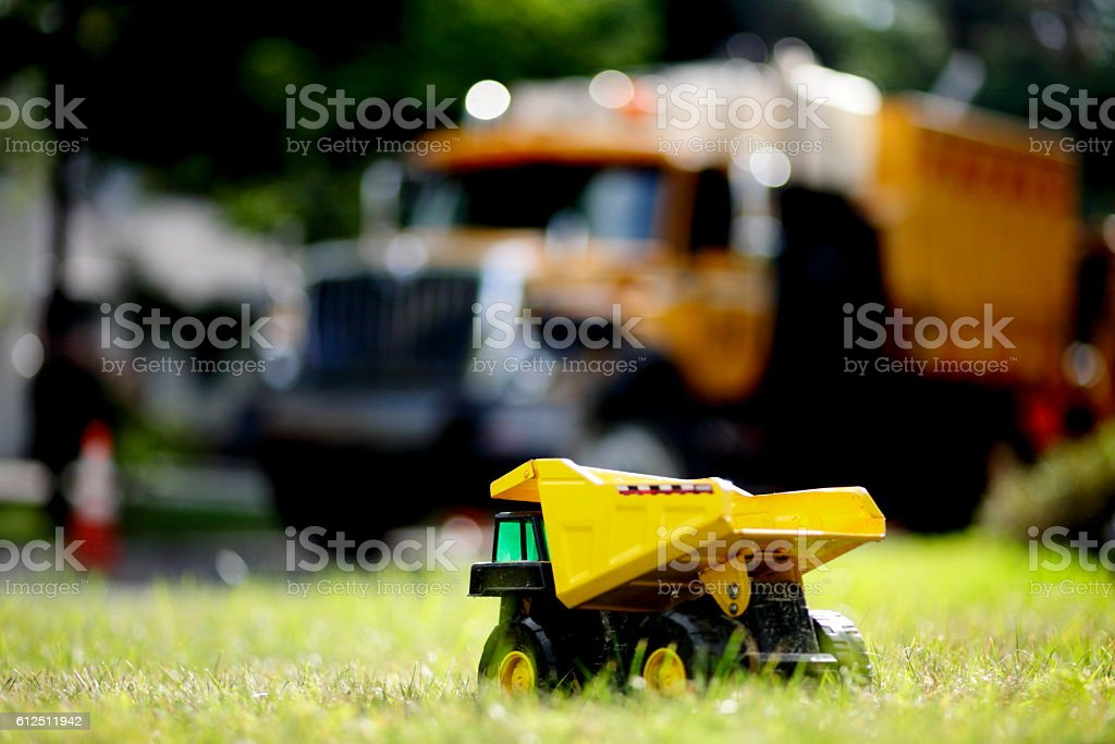 Toy truck versus real truck stock photo