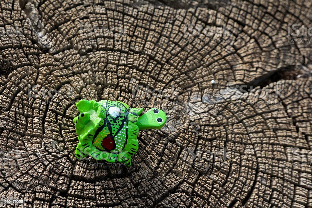 Toy turtle on the end of a wooden stump stock photo