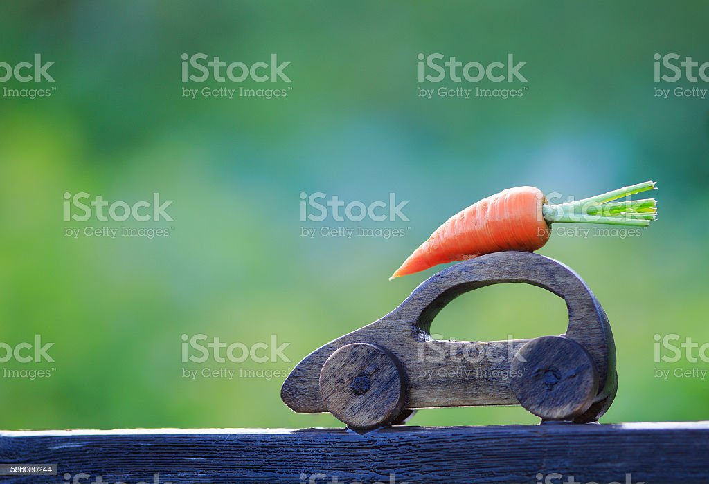 toy wooden car carries the carrot on the roof stock photo