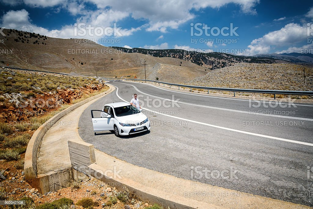 Toyota Auris and it's driver staying parked near road stock photo