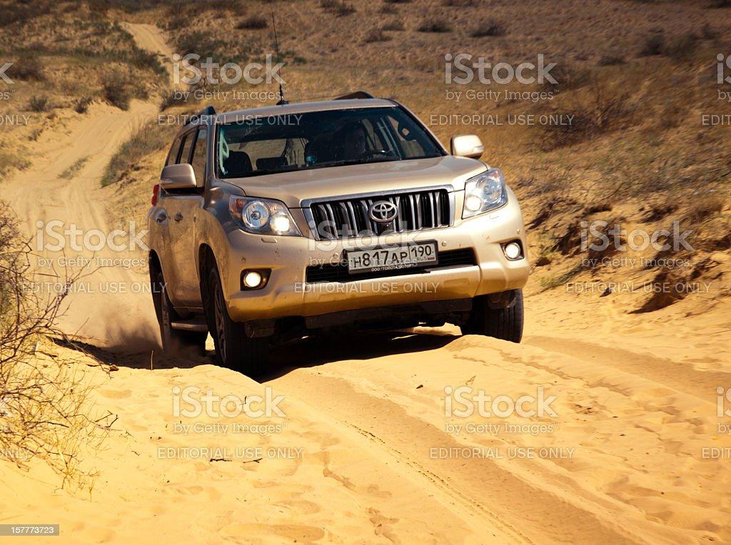Toyota Land Cruiser Prado 150 driving in sand desert royalty-free stock photo