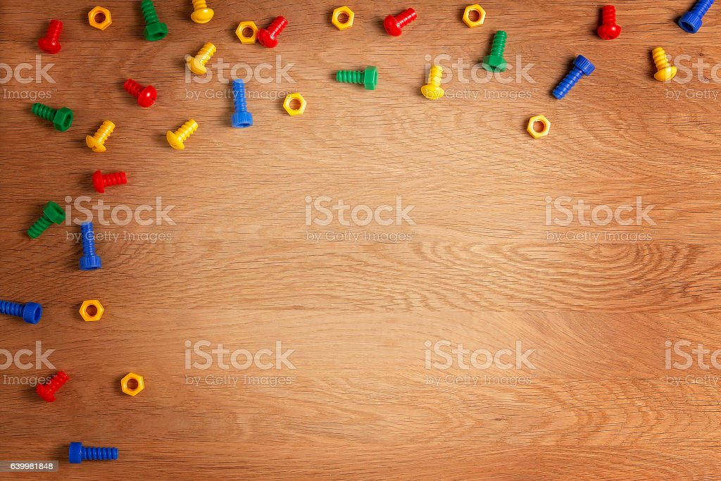 Toys Background Frame Boarder. Colorful nuts and bolts on wooden stock photo