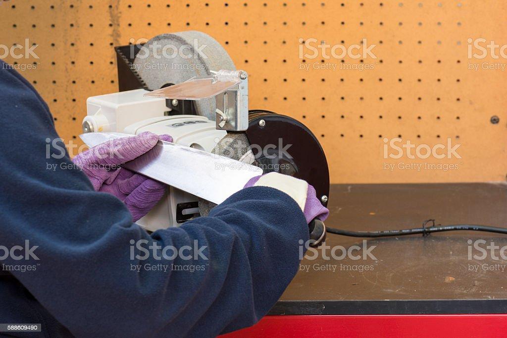 trabajador afilando cuchillo stock photo