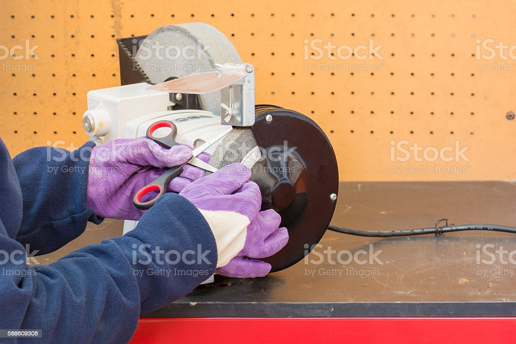 trabajador afilando tijeras stock photo