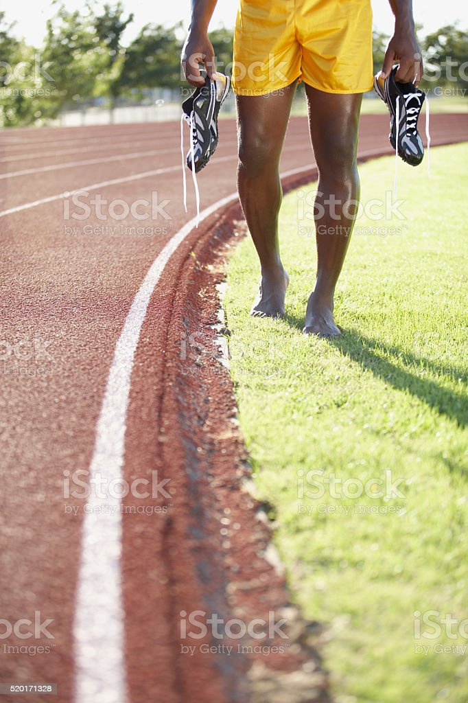 Track and field athlete holding his shoes stock photo