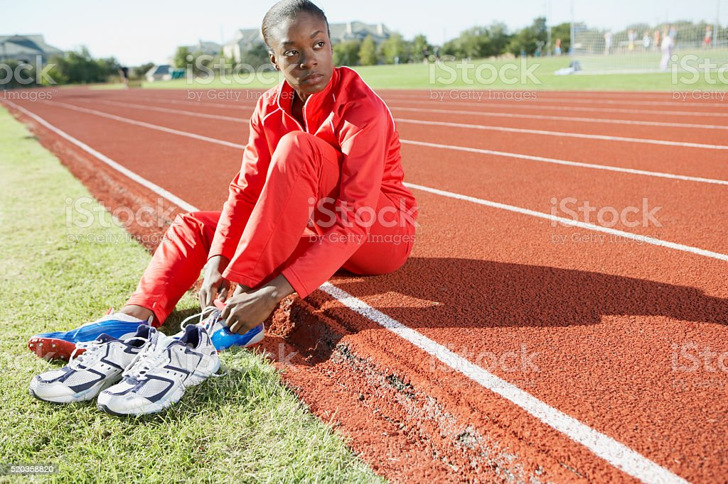 Track and field athlete putting on shoes stock photo