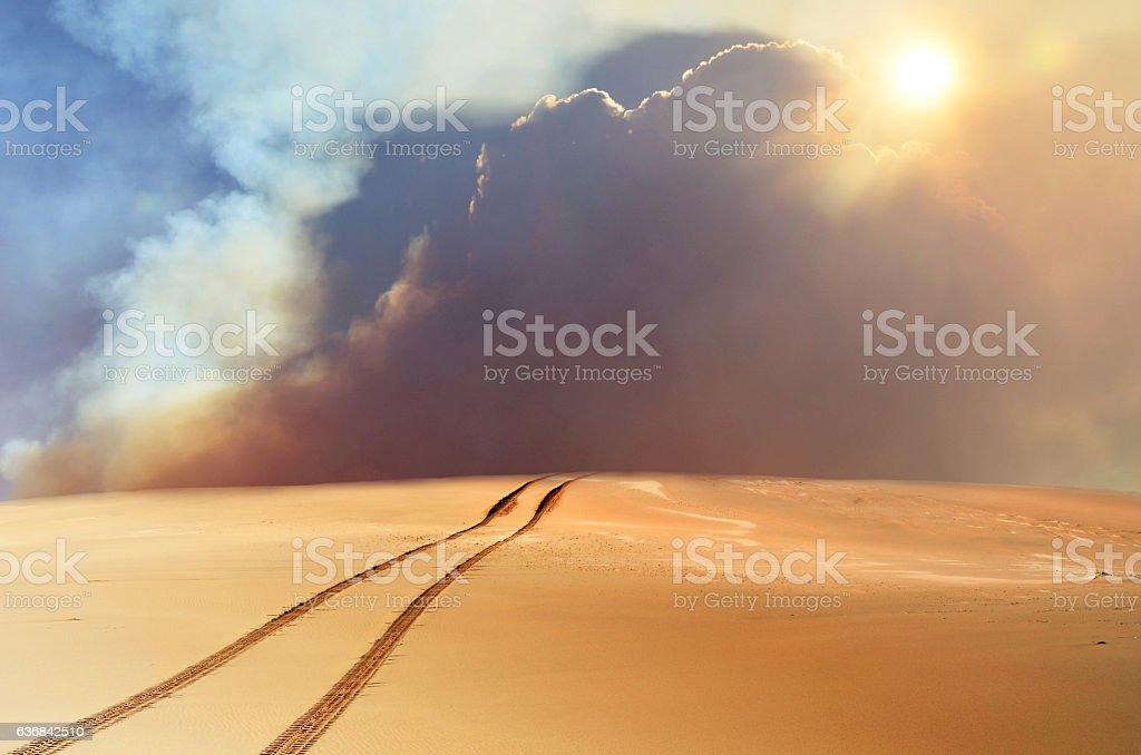 Tracks and storm over desert sand dune stock photo