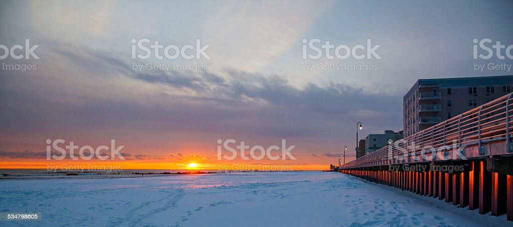 Tracks on snowy ground at sunset on Long Beach next to wall. stock photo