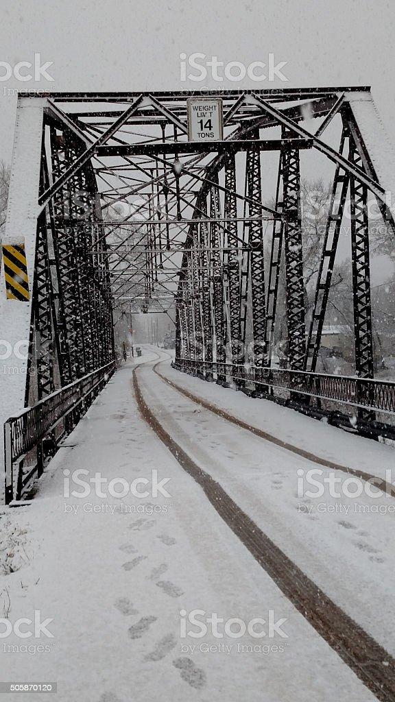 tracks through snow over historic Rockville Bridge Utah stock photo
