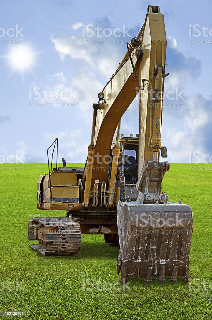 Track-type loader excavator machine on green grass field stock photo