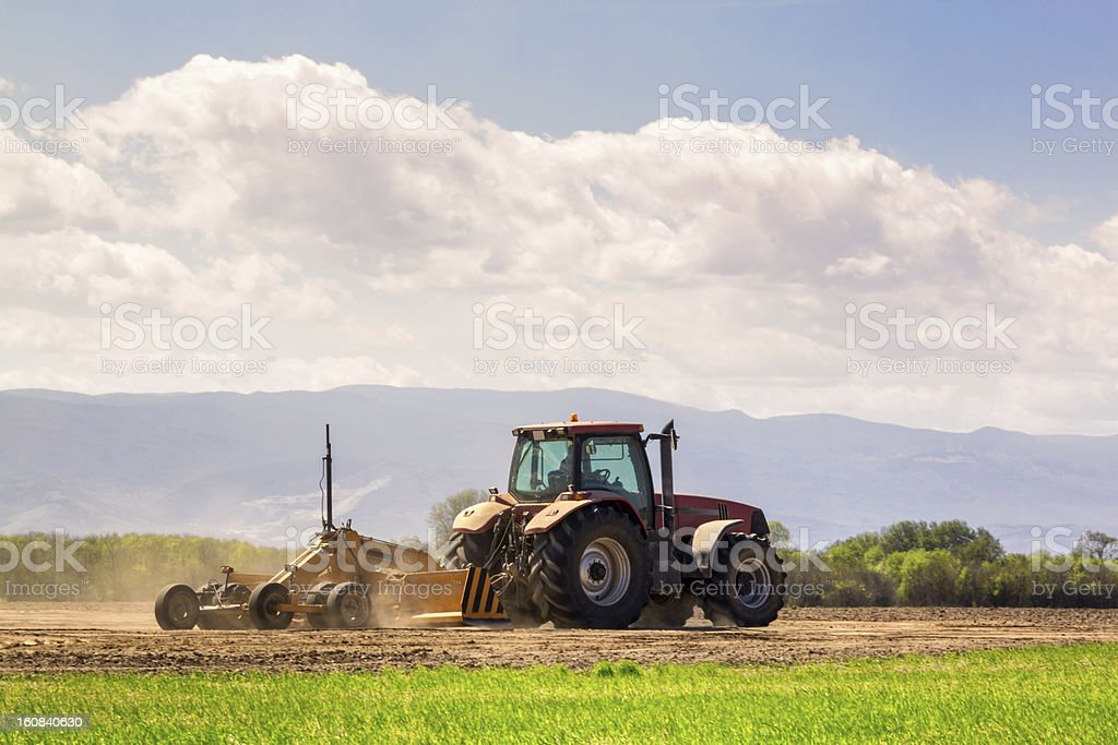 Tractor and laser guided land leveler royalty-free stock photo