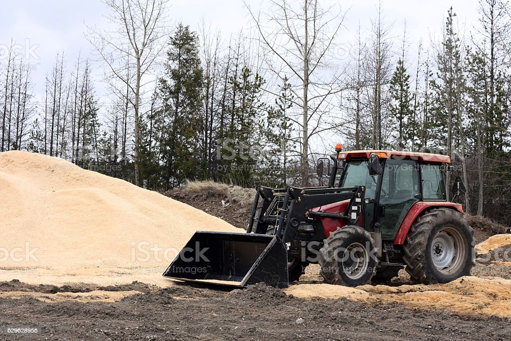 Tractor and Sawdust Pile stock photo