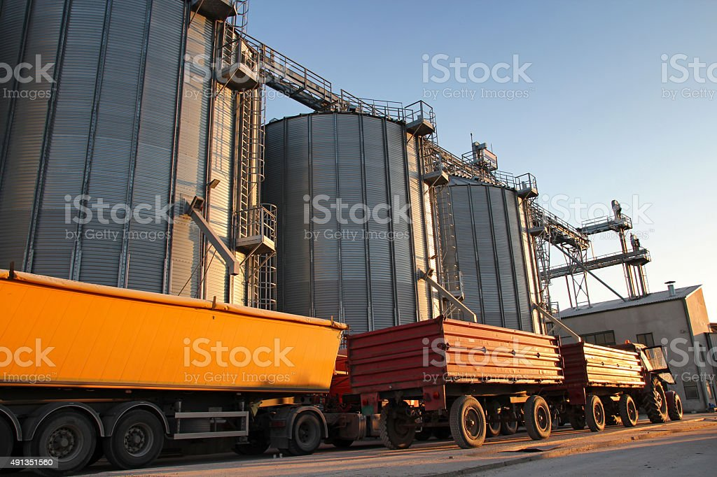 Tractor and Truck Beside Grain Silos stock photo