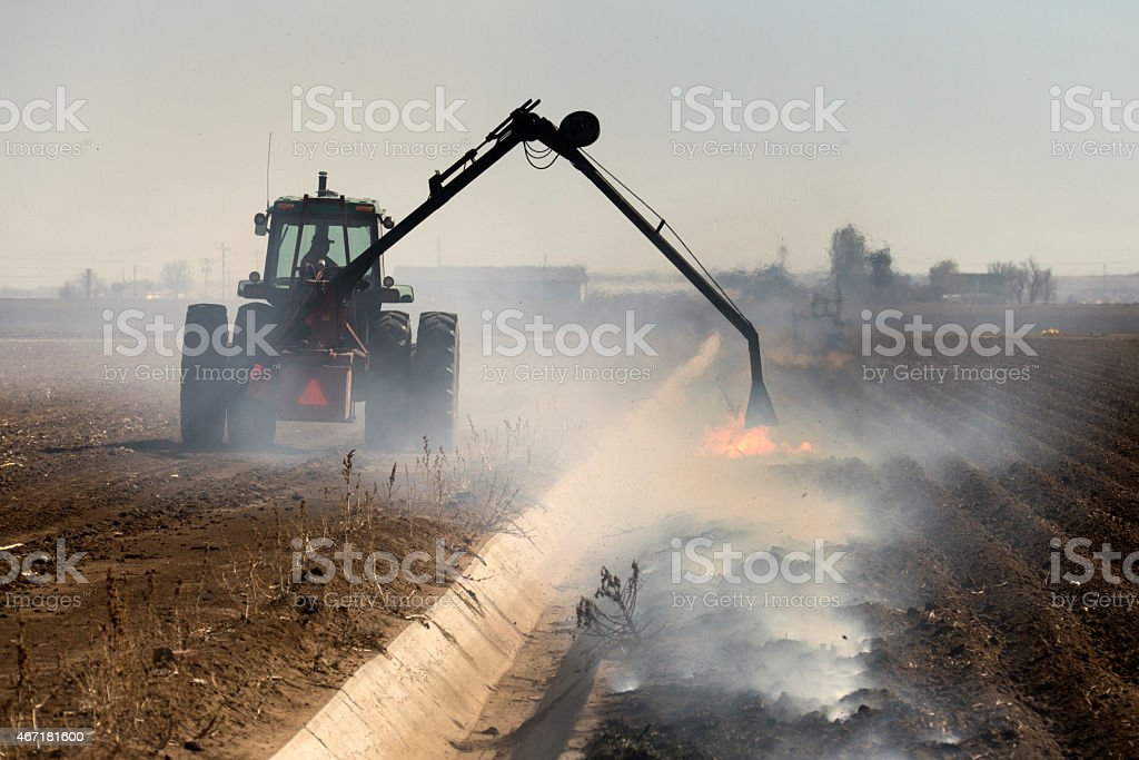 Tractor burns irrigation ditch weeds Greeley Colorado farm stock photo