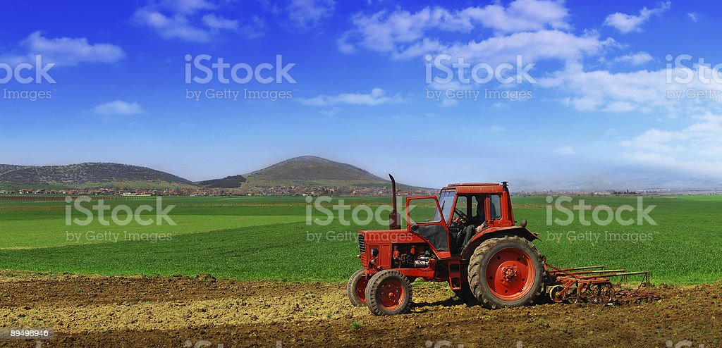 Tractor cultivating royalty-free stock photo