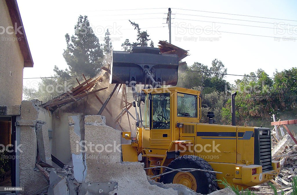tractor destroys old house stock photo