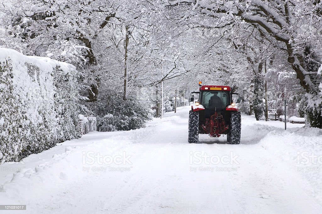 Tractor driving down a snow covered road royalty-free stock photo