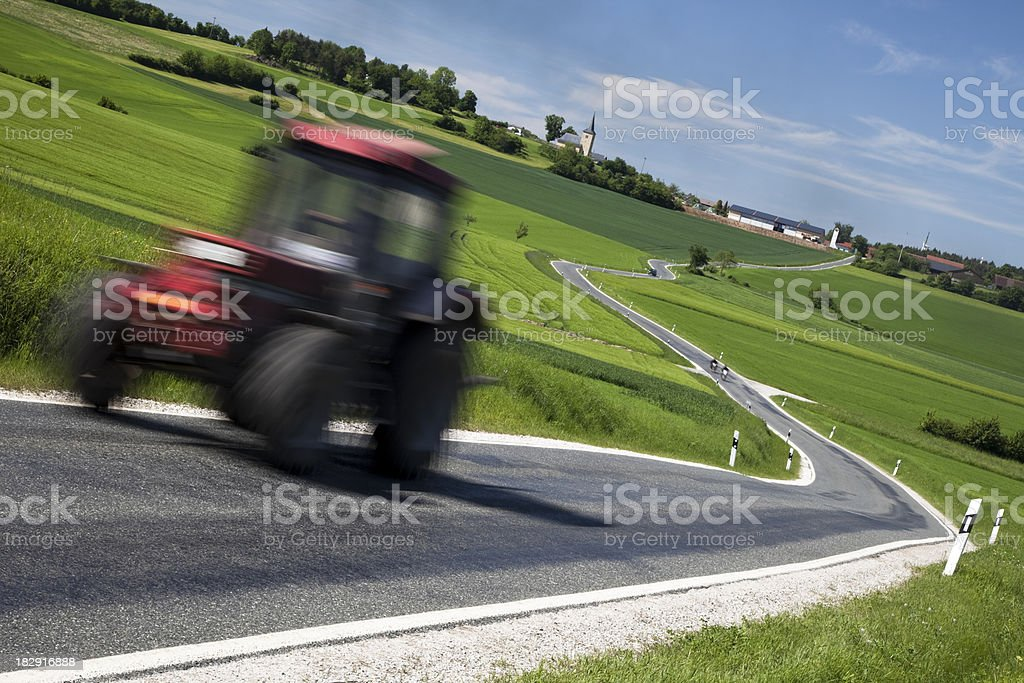 Tractor Driving on Rural Road in Spring stock photo