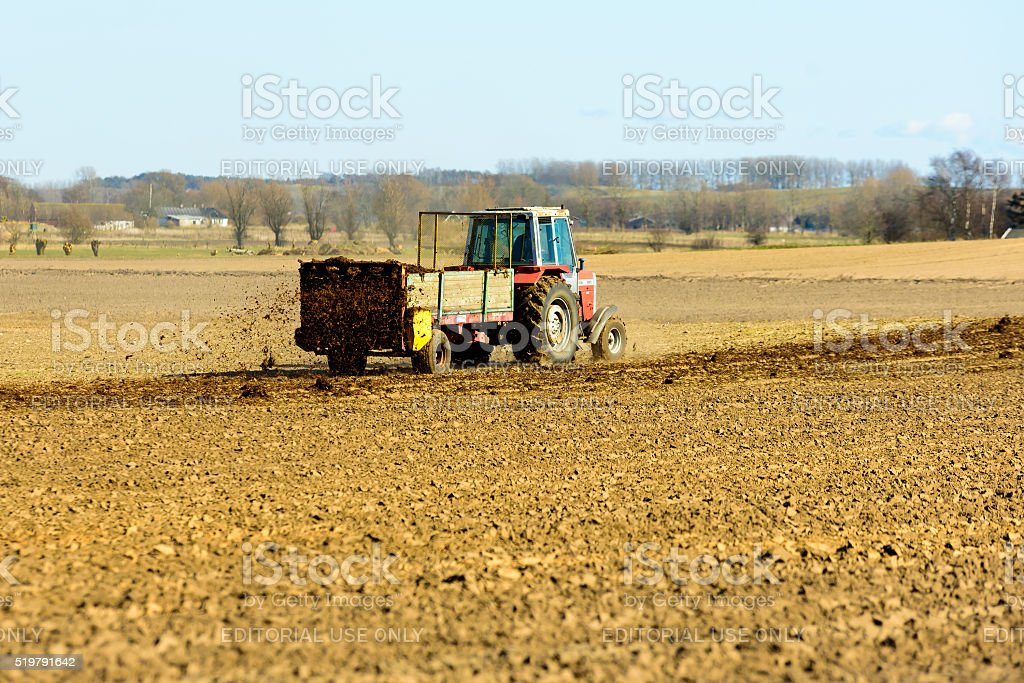 Tractor fertilizing a field stock photo