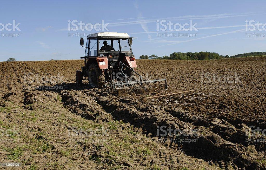 tractor harrowing a field stock photo