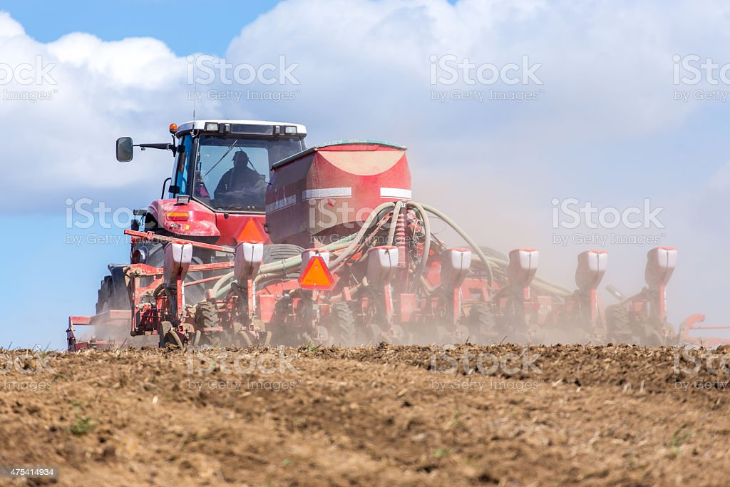 Tractor harrowing the field stock photo