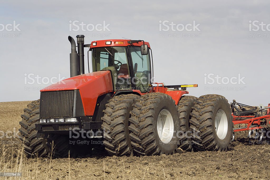 Tractor in Agricultural Farm Equipment in Field Harvesting Crop royalty-free stock photo