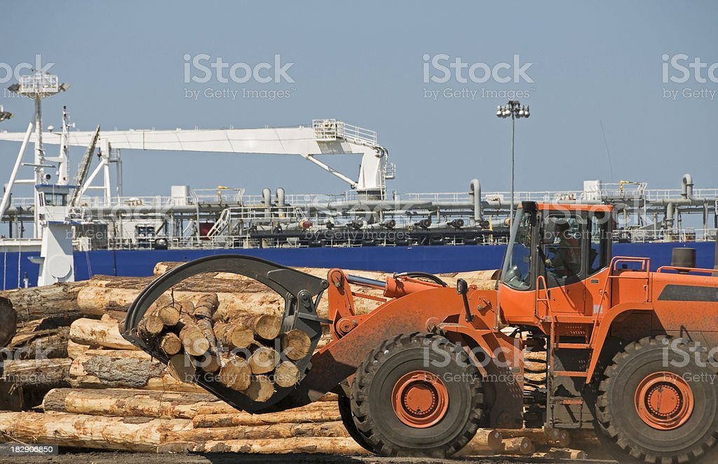 Tractor loading timber onto debarker stock photo