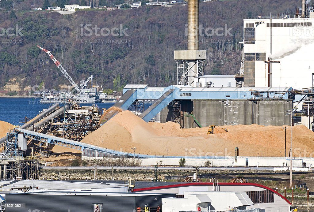 Tractor moving woodchips at pulp mill stock photo