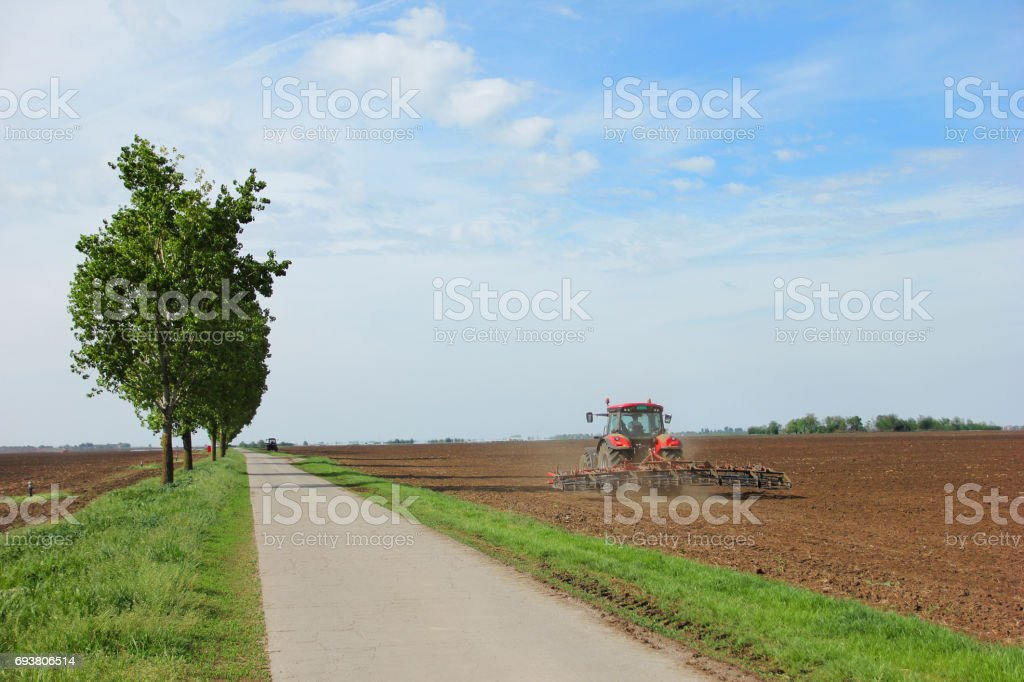 Tractor on a farm field working with a disc harrow stock photo