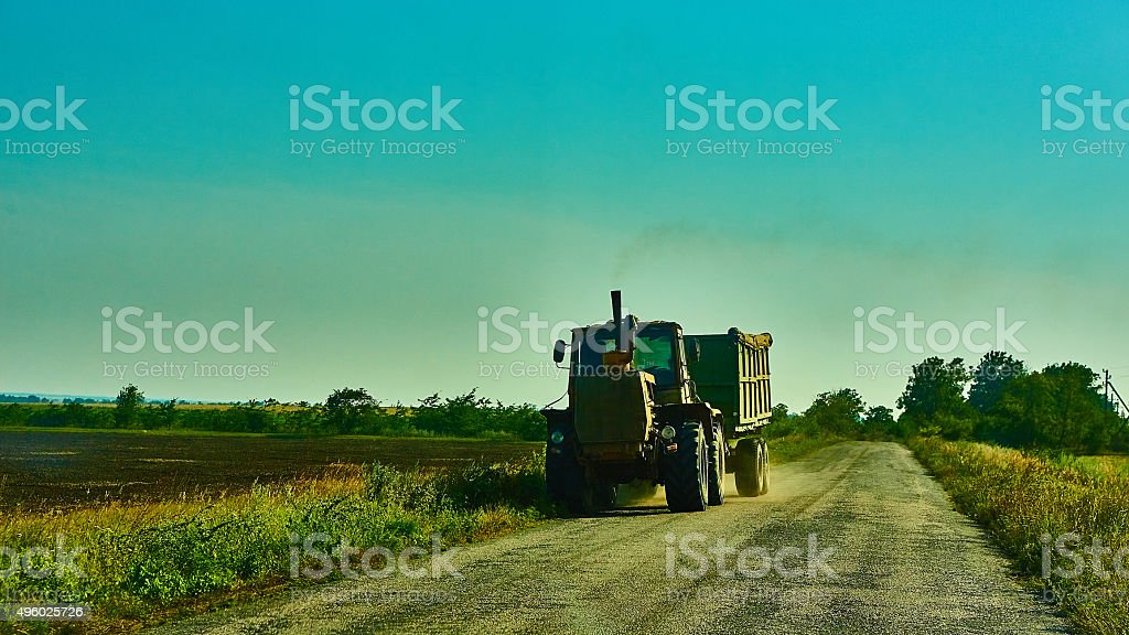 Tractor on the road with trailer stock photo
