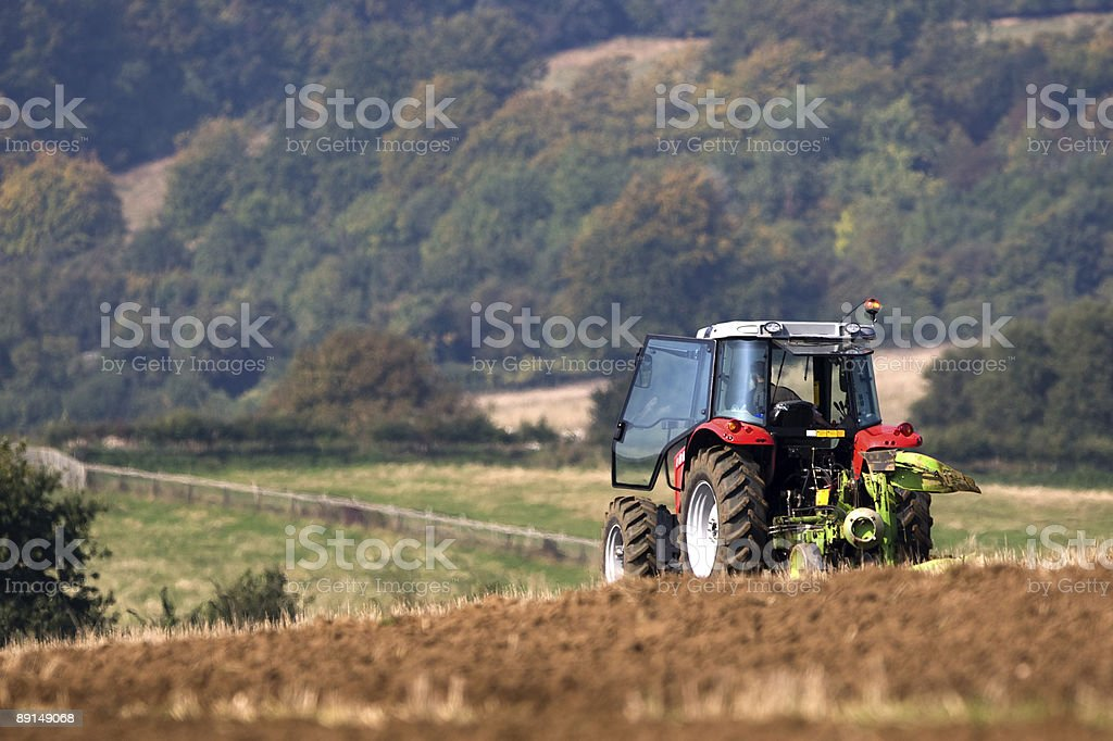 Tractor ploughing a field with a forest in the distance royalty-free stock photo