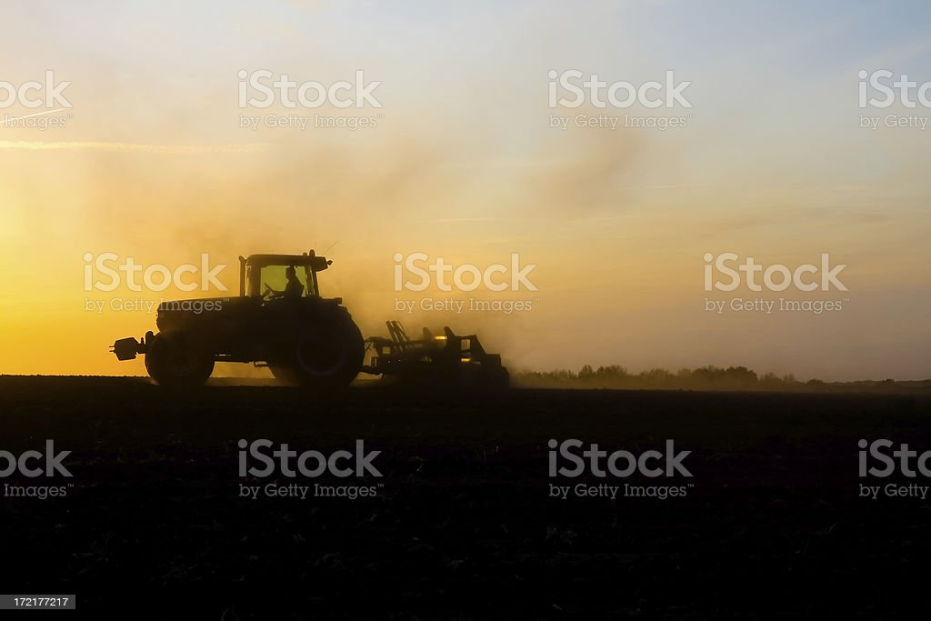 Tractor ploughing during sunset stock photo