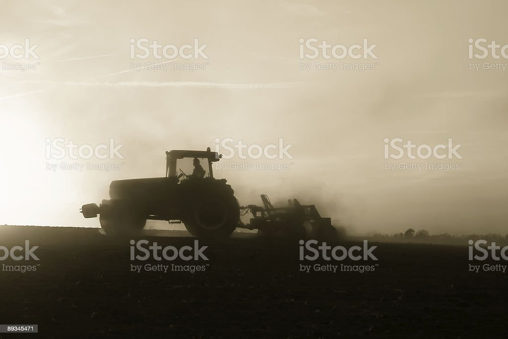 Tractor ploughing during sunset (B&W) stock photo