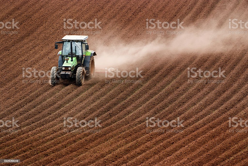 Tractor ploughing dusty field. royalty-free stock photo