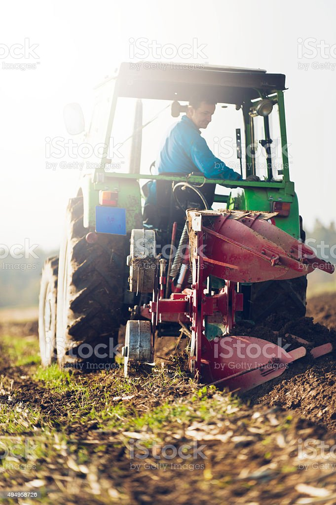 Tractor ploughing on the field in sunlight stock photo