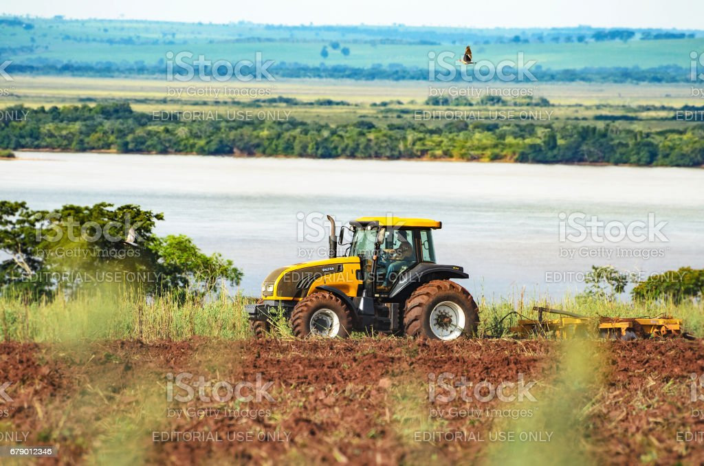 Tractor plowing and preparing the soil stock photo