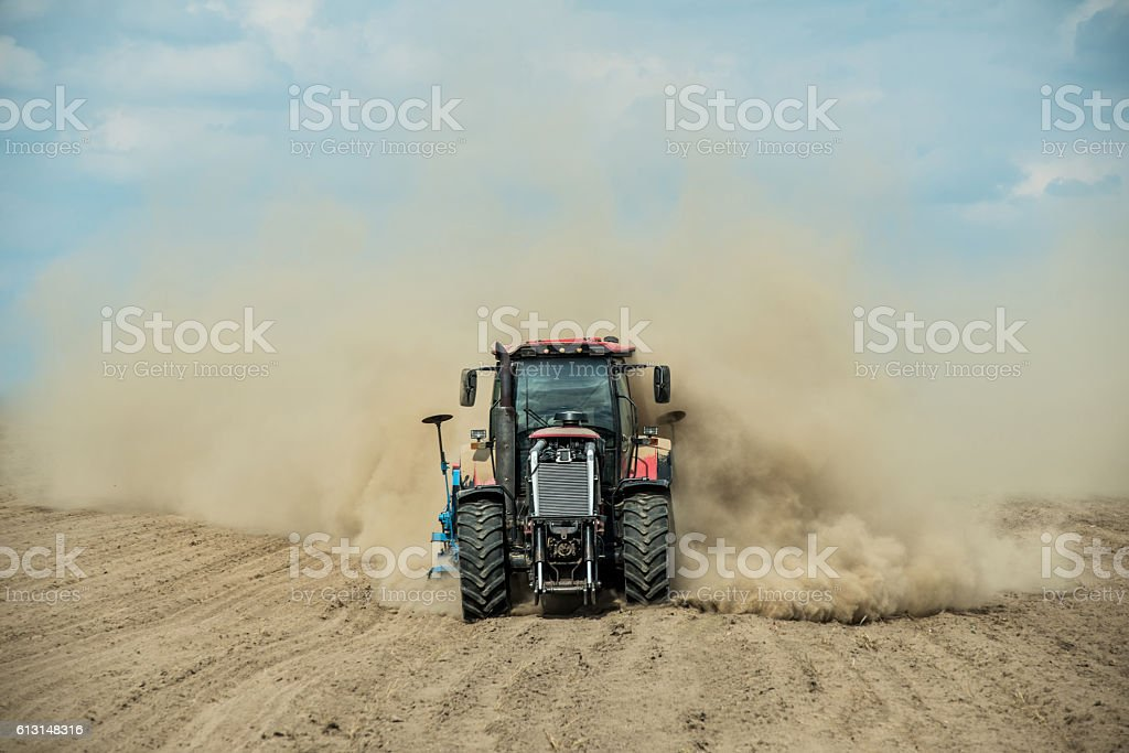 Tractor plowing dry farm land at autumn stock photo