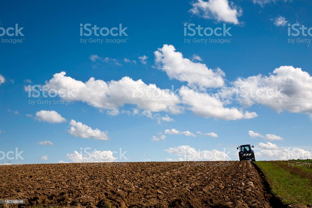 A tractor plowing the field for seeding under a blue sky stock photo