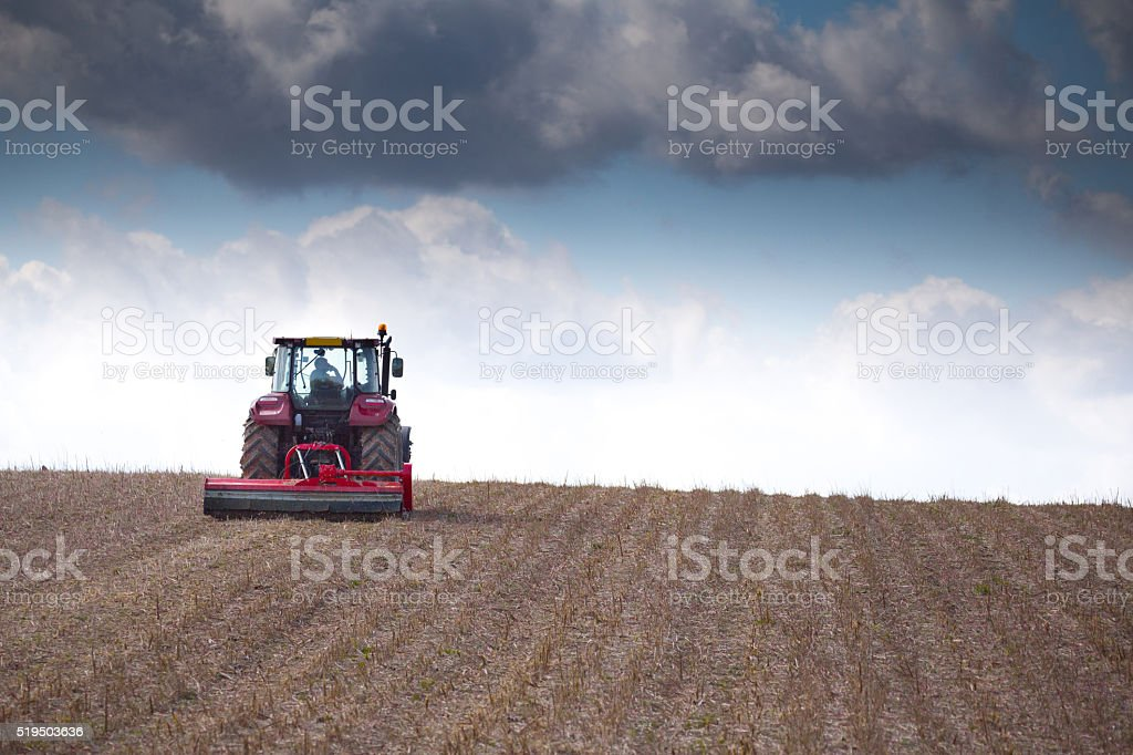 Tractor preparing the soil for spring crops stock photo