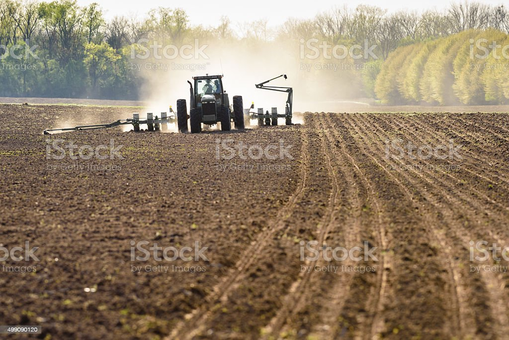 Tractor pulling a seeder doing spring planting. stock photo