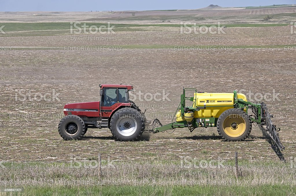 Tractor pulling fertilizer attachment across field royalty-free stock photo