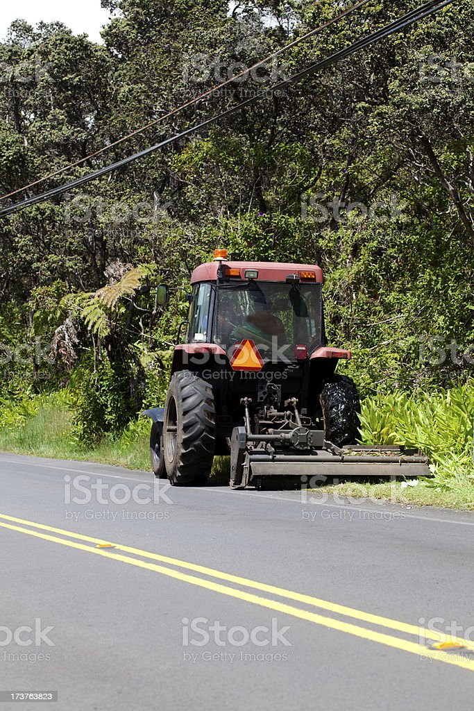 Tractor Pulling Lawn Mower Attachment Road Side royalty-free stock photo